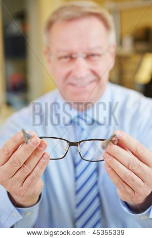 Happy smiling senior optician holding new glasses at consultation