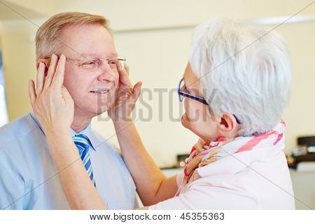 Senior man testing new rimless glasses at the optician