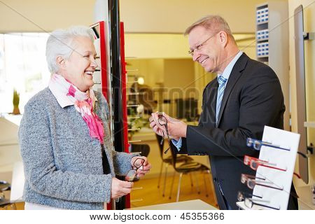 Optician helping senior woman finding new glasses