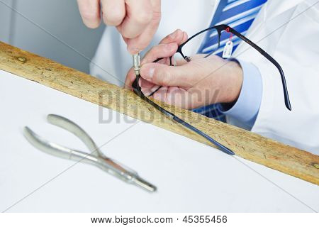 Optician fixing hinge of glasses with a screwdriver