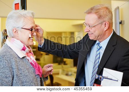 Elderly happy woman buying new glasses at optician store