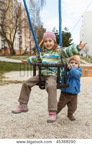 Brother And Sister Playing On The Swing