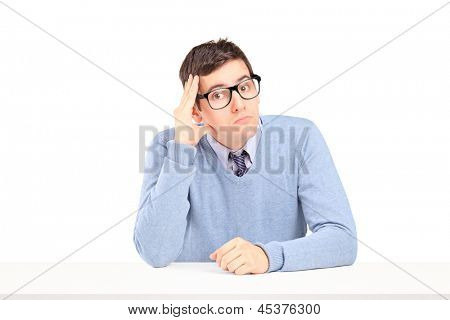 Doubtful guy sitting and thinking on a table isolated on white background