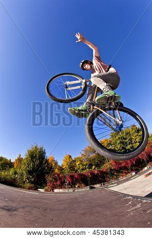 boy going airborne with his dirt bike and showing a non hander poster