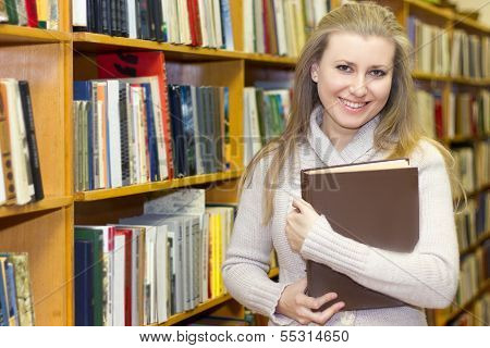 student standing at bookshelf in old library