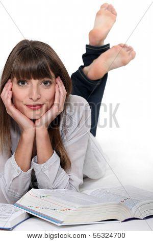 Relaxed girl reading encyclopedia
