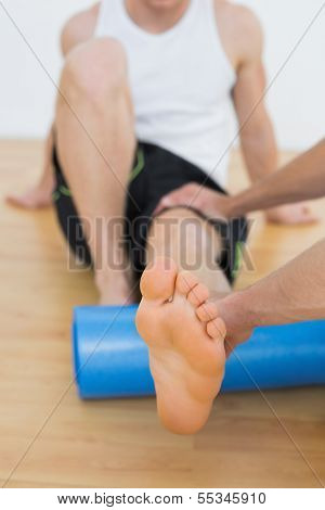 Physical therapist examining a young mans leg at the hospital gym