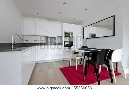 Contemporary Fully Fitted Kitchen In White With Modern Appliances And Dining Table For Four
