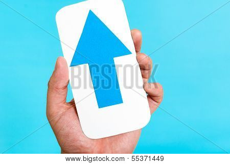 Uploading Content From Mobile Phone Concept. Hand holding a cellphone concept