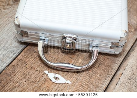 Aluminum Closed Suitcase With Keys On Wooden Floor
