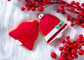 Christmas cookies Xmas red bell shape on white fur background