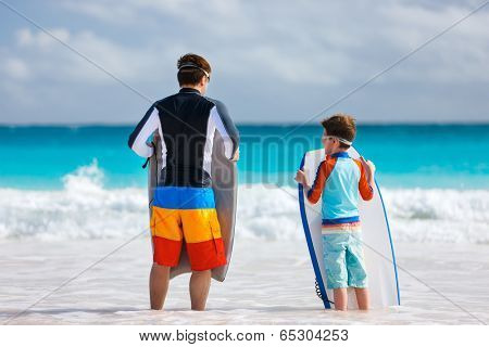Father and son at beach facing ocean with boogie boards