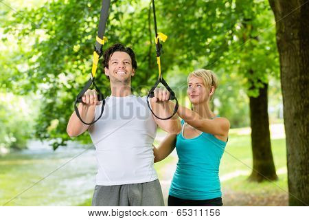 Young fitness man exercising with suspension trainer sling and personal sport trainer in City Park under summer trees