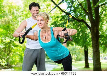 Fitness woman exercising with suspension trainer and personal sport trainer in City Park under summer trees
