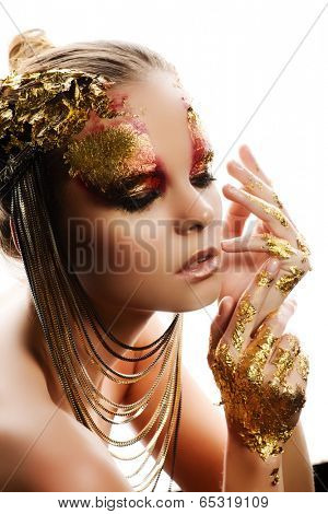 Art project: beautiful woman with golden make-up. Jewelry, make-up. Fashion. Isolated over white.