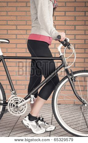Closeup of customized fixie bike and beautiful young sportive woman over a orange brick wall on the background poster