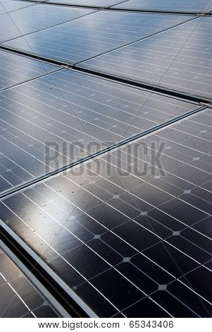Sun reflecting on roof mounted solar energy panels
