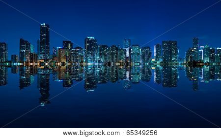 Miami skyline at night - panoramic image with beautiful water reflections