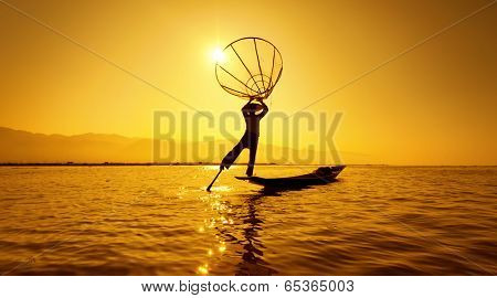 Burma Myanmar Inle lake fisherman on boat catching fish by traditional net. Outdoor sunset photography