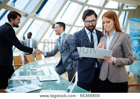 Two business people discussing data or planning work on background of their colleagues handshaking