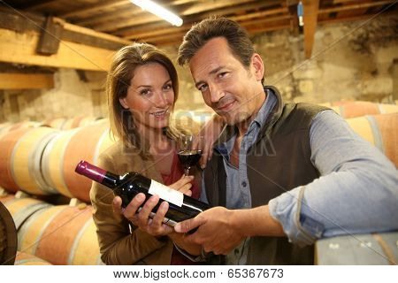 Cheerful couple of winegrowers in wine cellar