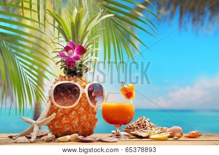 Ms ananas and a cup of cocktail on beach table