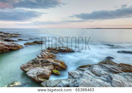 This is a long exposure HDR photo of a rocky coastal travel seascape. This was taken at Beavertail State Park in Jamestown Rhode Island USA. poster