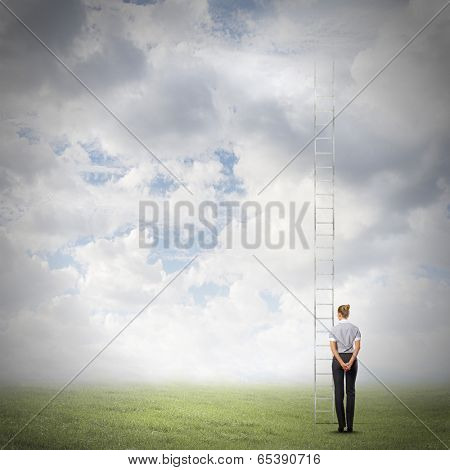 Rear view of businesswoman standing near ladder going high in sky
