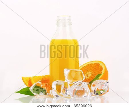 orange juice in the glass bottle, accompanied with fresh oranges and ice cubes