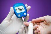 Doctor making blood sugar test. Hands with gloves on medical background poster