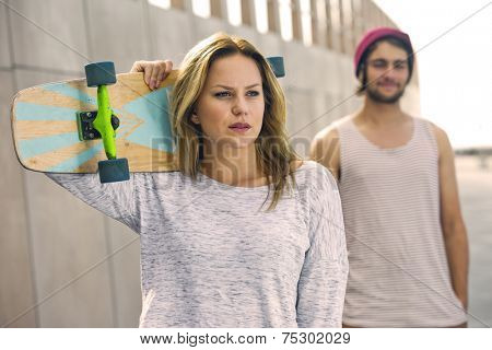 Young woman, carrying a skateboard on her shoulder, with her boyfriend standing behind her. A portrait of an independant personality, with an arrogant, confident air around her.