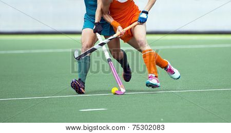 Two field hockey player, fighting for the ball on the midfield during an intense match on artificial grass poster