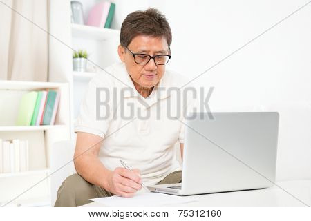 Portrait of mature Asian man using computer laptop and writing something on paper, sitting on sofa at home, senior retiree indoors living lifestyle.