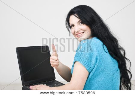 Woman Using Laptop And Giving Thumbs Up