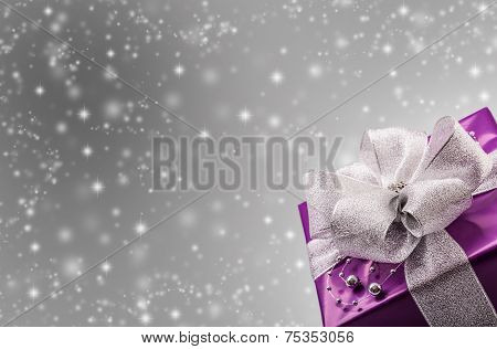 Christmas or Valentine's purple gift with silver ribbon abstract gray background.