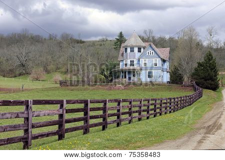 A rustic fence and dirt road by an old Victorian home under an overcast sky in the early spring.