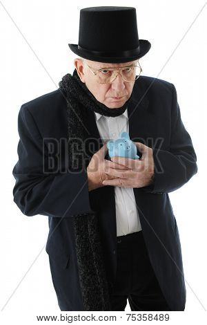A grumpy old man in a top hat clinging miserly to his blue piggy bank.  On a white background.