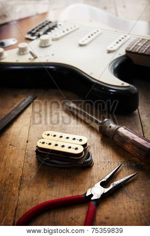 Electric guitar repair. Electric guitar and double coil pickup and tools.