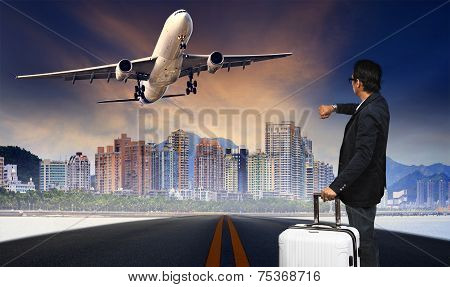 Man With Big Luggage Standing On Raod And Watching To Airplane Flying Over Urban Scene