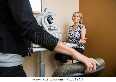 Mature female optician asking patient to sit in eye clinic