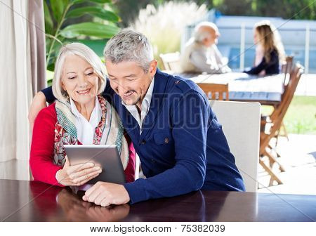 Happy grandmother and grandson using digital tablet with family in background at nursing home