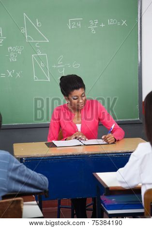 African American teacher writing in binder at desk with students in foreground