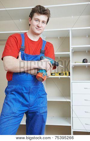 Portrait of happy carpenter worker in front of home built-in cupboard