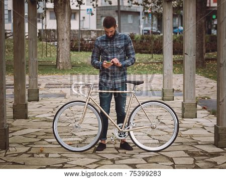 Hipster Man With A  Bike And Smartphone