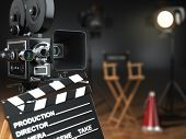 Video, movie, cinema concept. Retro camera, flash, clapperboard and director's chair in dark studio with dof effect. 3d poster