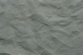 the abstract textured background from crumpled mesh with small cells synthetic fabric of silvery color poster