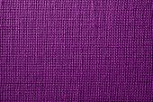 the textured background of synthetic fabric with crisscross fibers of dark lilac color poster