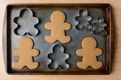 High angle shot of an old baking sheet with Christmas gingerbread man cookies and cookie cutters. Ho