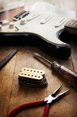 Electric guitar repair. Electric guitar and double coil pickup and tools. poster