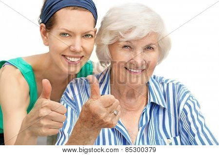 Happy senior woman portrait together with granddaughter, holding thumb up
